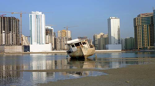 The photo shows an old-style dhow on the sand flats with gleaming white skyscrapers behind, and next to this a building under construction surrounded by cranes.
