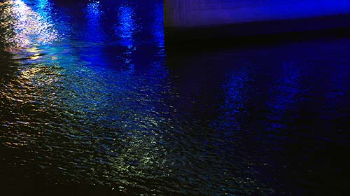 Blue and gold colours. The photo shows deep blue luminous colours of the reflections on the water from the neon signs above the river.